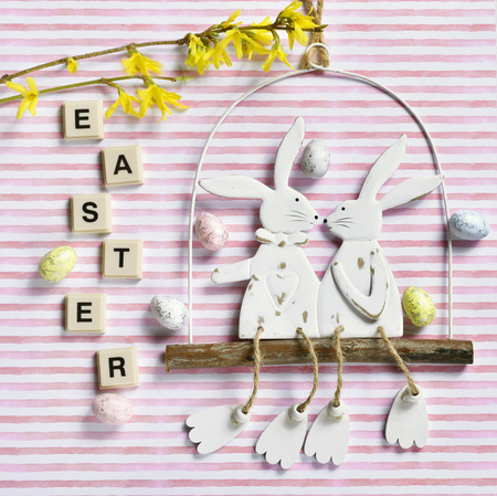 easter flat lay with funny bunnies decor, forsythia flowers and letter tiles on striped background Stockfoto - 119888847