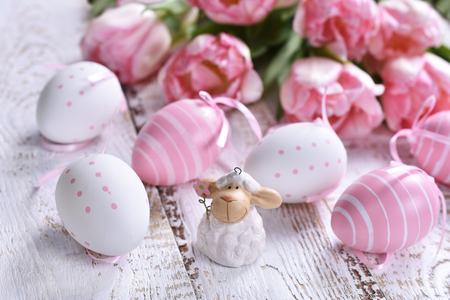 easter decoration with painted eggs,lamb figurine and pink tulips lying on white wooden table Stockfoto - 120551476