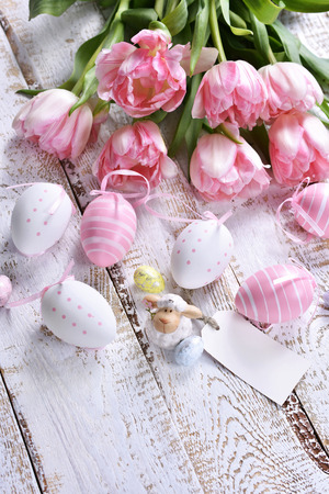 easter decoration with painted eggs,lamb figurine and pink tulips lying on white wooden table Stockfoto - 120551479