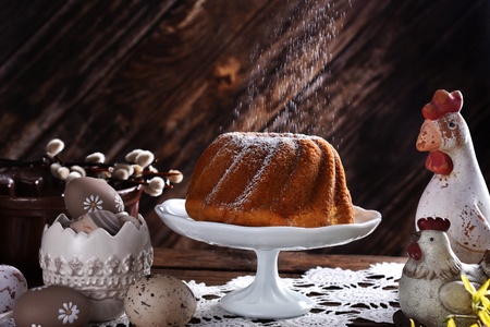 easter ring cake with falling powdered sugar on festive table in rustic style Stockfoto - 120551643