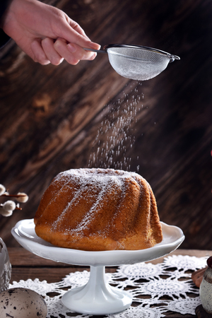 a hand with strainer sprinkling powdered sugar on easter ring cake on festive table in rustic style