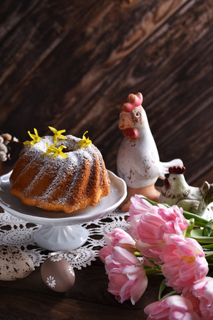 easter ring cake with powdered sugar and forsythia flowers on the top on festive table in rustic style