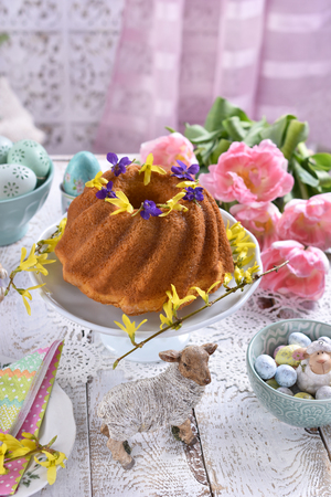 easter festive table with pink tulips, decorations and traditional ring cake in pastel color arrangement Stockfoto - 120544555