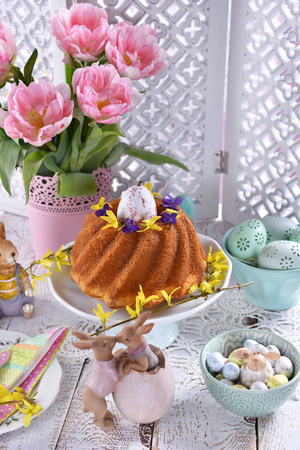 easter festive table with pink tulips, decorations and traditional ring cake in pastel color arrangement