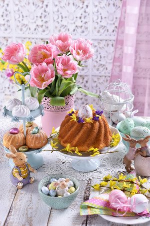 easter festive table with pink tulips, decorations, traditional ring cake, muffins in pastel color arrangement Stockfoto - 120544562