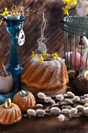 easter ring cake with powdered sugar and muffins on festive table in vintage style