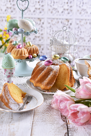 easter ring cake with powdered sugar and muffins on festive table