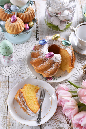 easter ring cake with powdered sugar and muffins on festive table Stockfoto - 120544566
