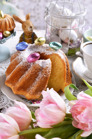 easter ring cake with powdered sugar and muffins on festive table Stockfoto - 120544569