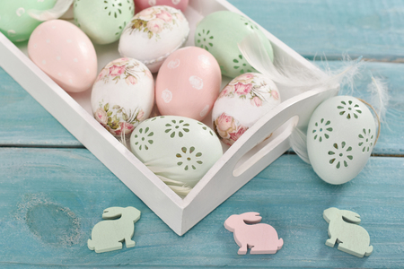 easter background with colorful eggs in a wooden tray