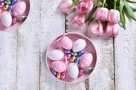 easter flat lay with painted eggs in round box and pink tulips lying on white wooden table
