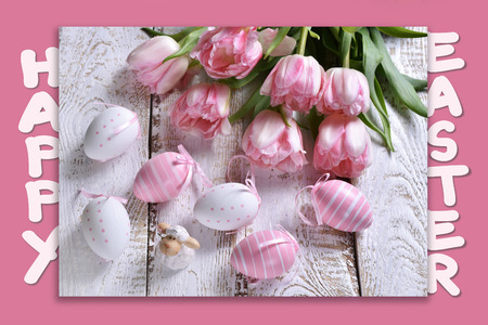 easter card with greeting text, painted eggs, lamb figurine and pink tulips on pink background