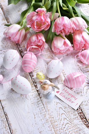 easter decoration with painted eggs,lamb figurine and pink tulips lying on white wooden table