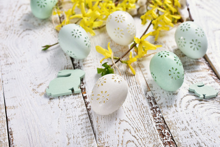 easter decoration with painted eggs and forsythia flowers lying on white wooden table