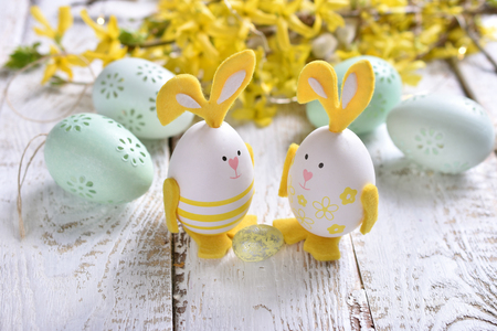 easter decoration with eggs with bunny ears, mint eggs and forsythia flowers lying on white wooden table Banco de Imagens