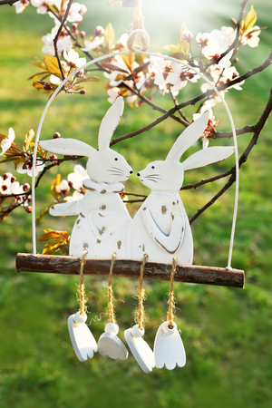 easter picture with spring blooming trees and two bunnies swinging decor Stockfoto - 123715317