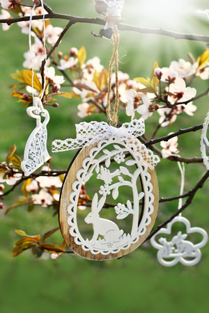 white wooden easter decorations hanging on trees in spring blooming garden