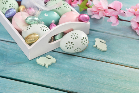 easter background with colorful eggs in white tray on blue wooden planks and copy space for own text