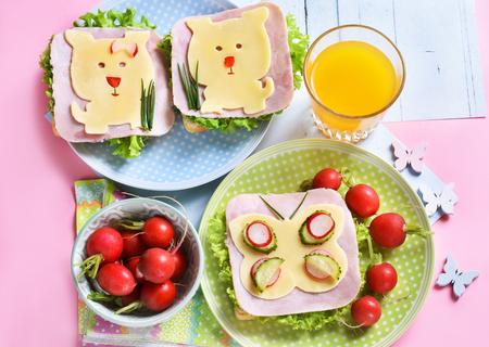 healthy breakfast for kids with funny sandwiches with cheese dog and butterfly shapes ,radish and juice Stockfoto - 123714265