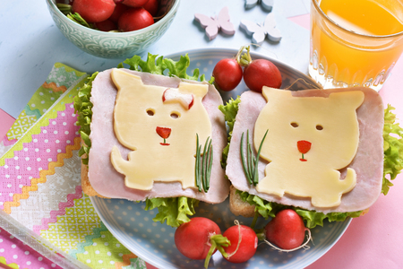 healthy breakfast for kids with funny sandwiches with cheese dog shape, ham and radish