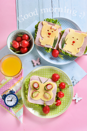 healthy breakfast for kids with funny sandwiches with cheese dog and butterfly shapes ,radish and juice Stockfoto - 123714264