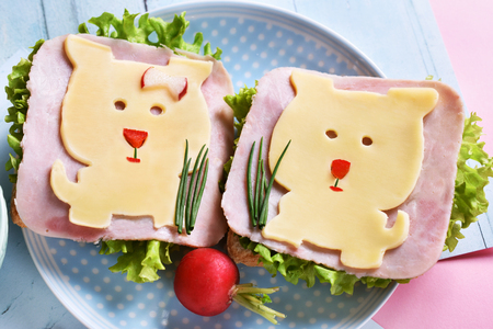 healthy breakfast for kids with funny sandwiches with cheese dog shape, ham and radish Stockfoto - 123714273