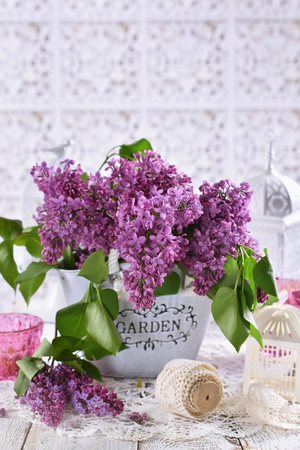 bunch of purple lilac flowers on the table in shabby chic style interior