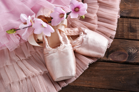 pink ballet pointe shoes with magnolia flowers and tulle dress on wooden background Stockfoto