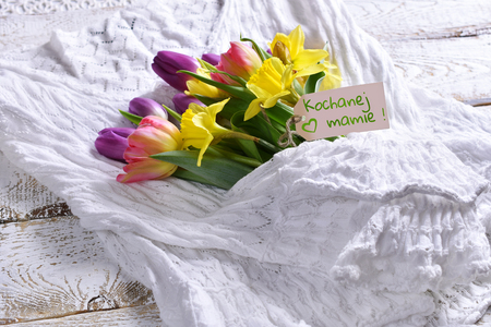 bouquet of spring flowers with a paper tag with greetings for mom lying on white sweater with  sleeves hugging the bunch Stockfoto - 123715169
