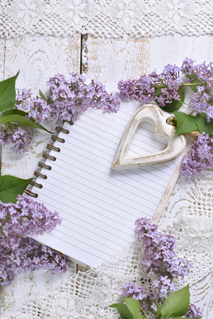 romantic style flat lay with purple lilac, a heart and a notebook with space for own text on white wooden background Stockfoto - 123715172