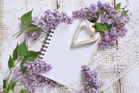 romantic style flat lay with purple lilac, a heart and a notebook with space for own text on white wooden background