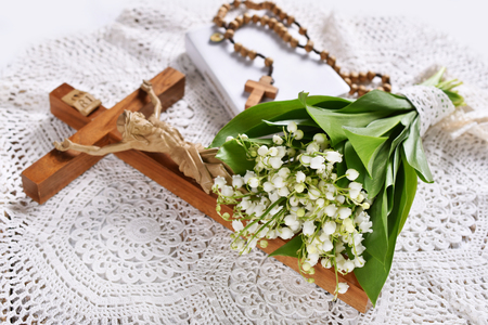 First communion or baptism composition with prayer book, rosary, cross and flowers lying on the table Stockfoto - 123715173