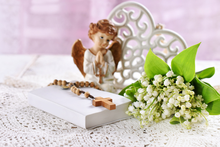 First communion or baptism composition with prayer book, rosary, angel and flowers lying on the table