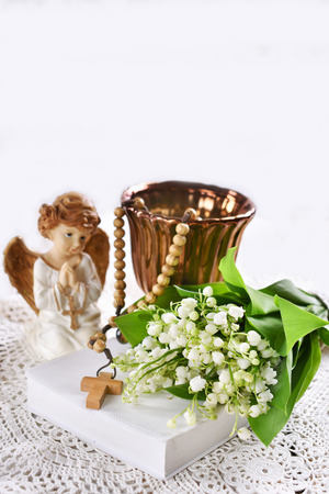 First communion or baptism composition with prayer book, rosary, angel and flowers on white background Stockfoto - 123715175