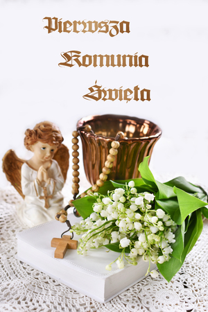 First holy communion composition with prayer book, rosary, angel and flowers on white background