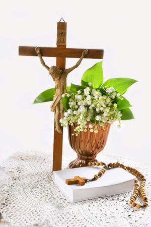 First communion or baptism composition with standing cross, prayer book, rosary, chalice and flowers on white background Stockfoto - 123715180