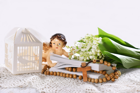 First communion or baptism composition with prayer book, rosary, angel and flowers on white background