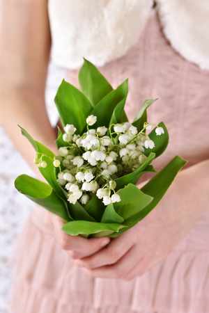 elegant young girl holding a bunch of lily of the valley flowers she received or wants to give
