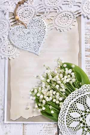 vintage style flat lay with bunch of lily of the valley flawers,old paper, a heart and laces