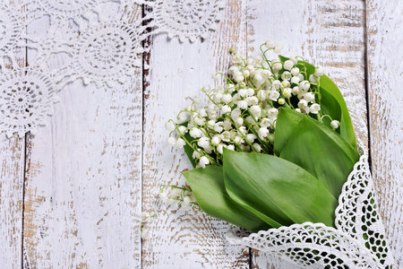 white wooden background with a bunch of lily of the valley flowers lying in the corner Stockfoto - 123715184