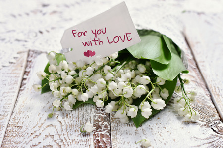 bunch of lily of the valley flowers with love text on paper label lying on the table Stockfoto