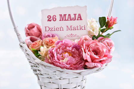 a big wicker basket of flowers for a mom with text in polish Stockfoto - 123715052