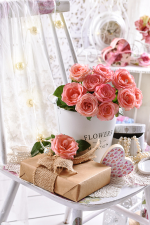 beautiful bunch of pink roses and a gift on the chair in romantic vintage style