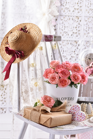 beautiful bunch of pink roses and a gift on the chair in shabby chic style interior Banco de Imagens