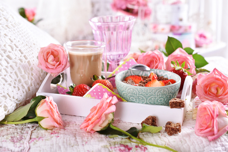 healthy and diet breakfast with yogurt, strawberries and muesli with coffee in bed covered with roses in romantic style