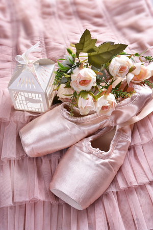 flat lay with pink ballet pointe shoes and roses lying on tulle dress