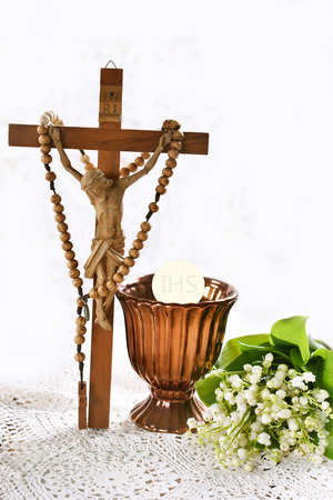 First communion or baptism composition with standing cross, rosary, chalice and flowers on white background