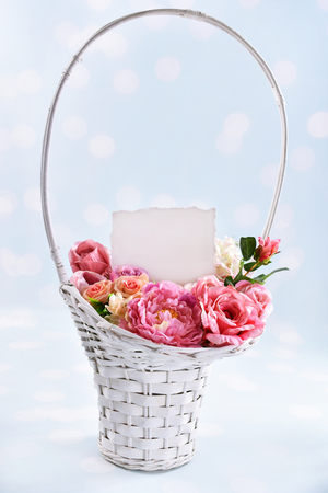 a big wicker basket of flowers for a loved one with a blank card for own greeting text Banco de Imagens