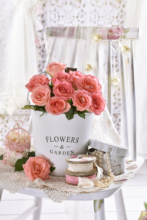 beautiful bunch of pink roses sitting on the chair in a shabby chic style interior