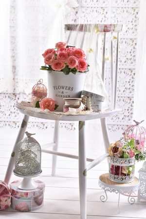 beautiful bunch of pink roses standing on the chair in shabby chic style interior